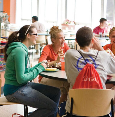SUNY Cortland students sit and talk at a cafe table.