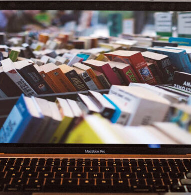 Laptop on table with a picture of hardcover books on screen.