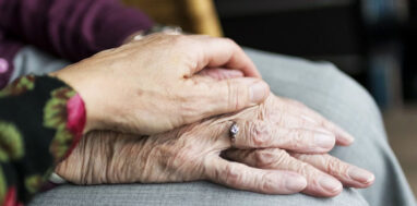A senior citizen's hand is on its lap being held under a younger person's hand.