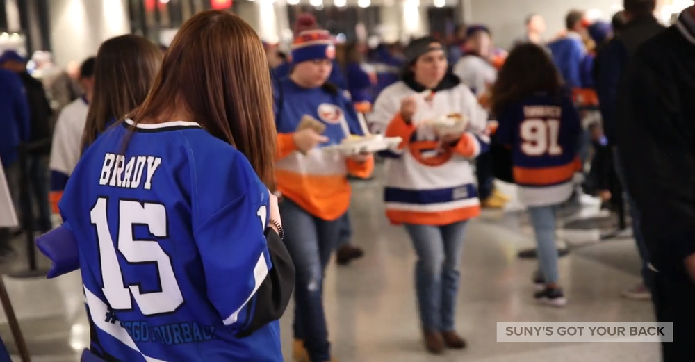 NY Islanders fans walk the concourse at a game with someone in a SUNY's Got Your Back jersey in the foreground.