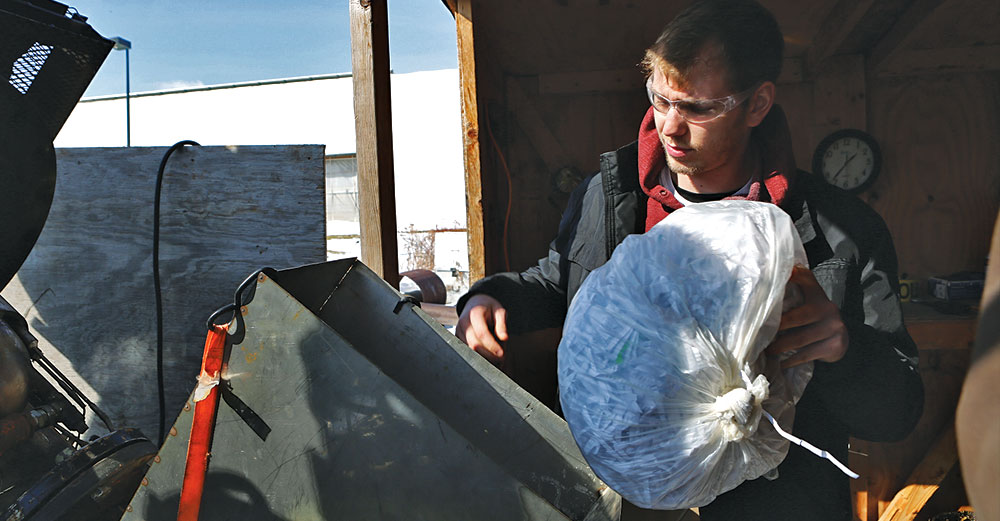 A male inserts paper waste into a metal bin outdoors.