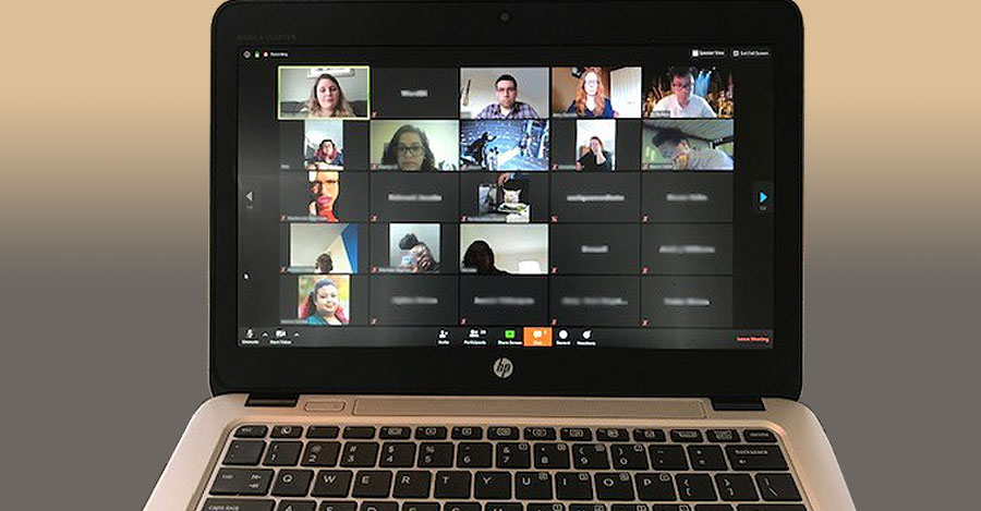 A laptop shows a student virtual mmeeting taking place on Zoom.