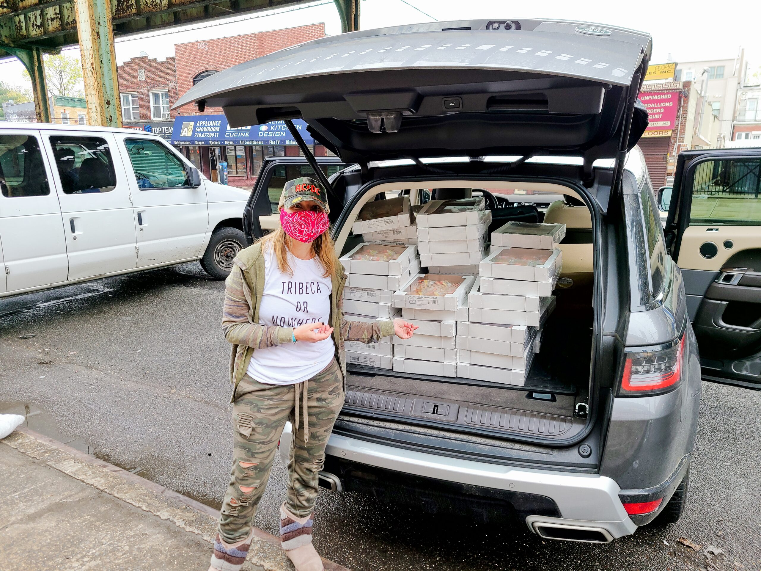 A woman stands near an SUV packed with boxes for a Food For The Frontline drop-off event.