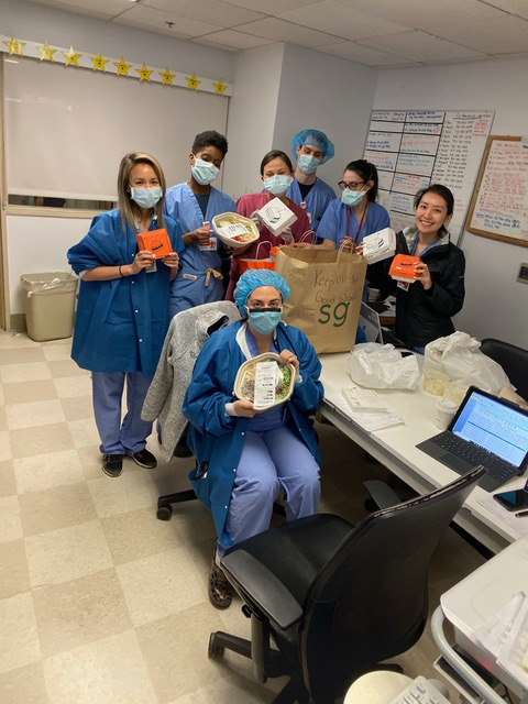 Medical frontline workers show off their packaged meals inside a hospital break room.