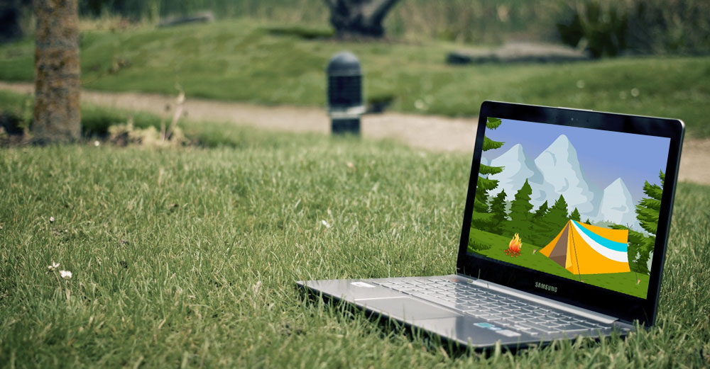 A laptop placed on the grass in a park with a screen showing a camping tent.