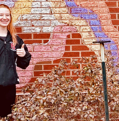 Student Hunter Crawley smiles in front of brick wall.