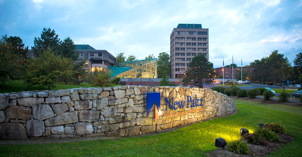 Stone entrance sign to SUNY New Paltz campus with lights on it during twilight hour.