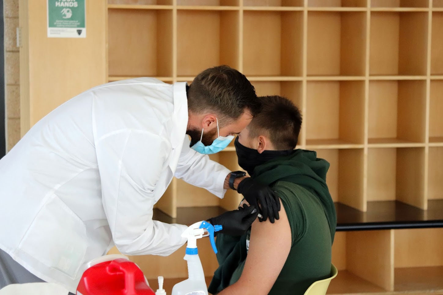 A male student receives a flu shot in the arm from a doctor in white coat.