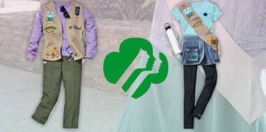 Two girl scouts outfits with girl scouts logo between them.