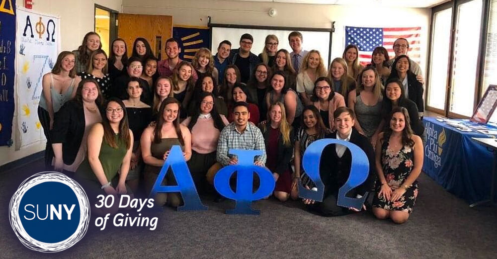 Members of the SUNY New Paltz student-led chapter of Alpha Phi Omega pose in front of the greek letters.