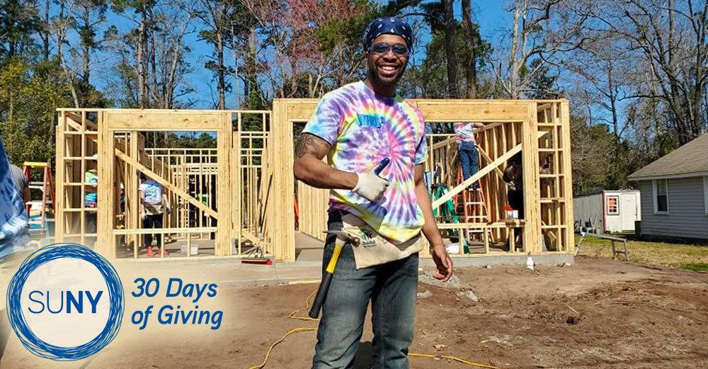 Alfred State student Christopher Phillips gives a thumbs up while working to build a house with Habitat for Humanity in Myrtle Beach, SC.