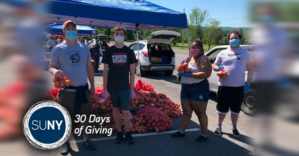SUNY Cobleskill students stand in parking lot during mobile food drive.
