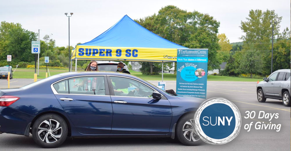 A blue car pulls up to a canopy tent in a parking lot at a socially distanced job fair.