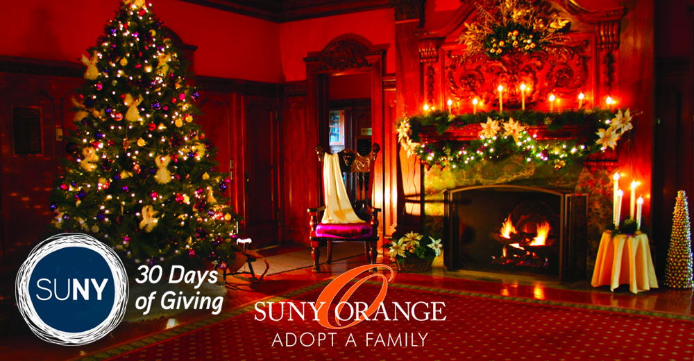 Formal room with christmas tree, fire in fireplace, and decorations hung with SUNY Orange Adopot A Family logo