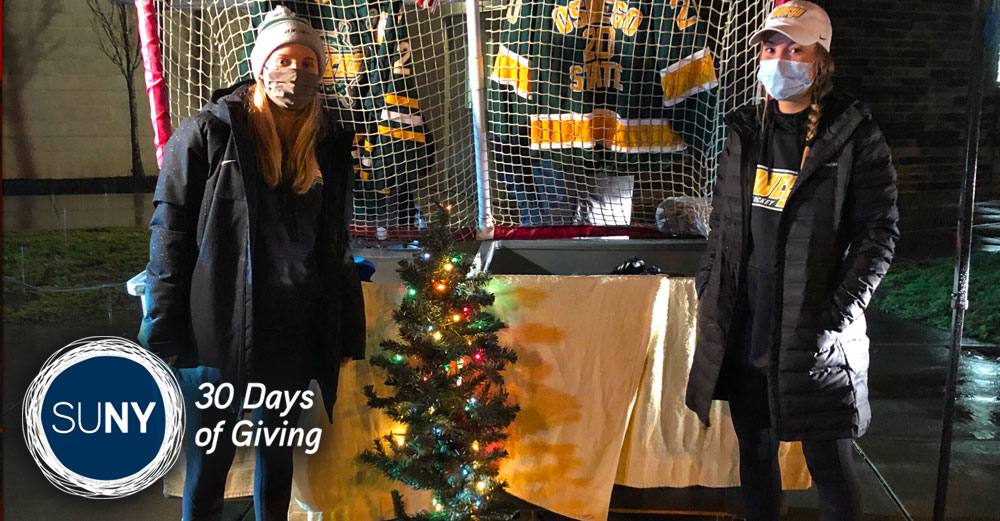 Two female SUNY Oswego students outside at night in front of hockey net and mini christmas tree.