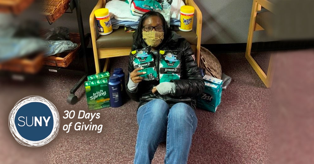 Female student sits on the ground holding various bath soaps and care items that are part of a donation effort.