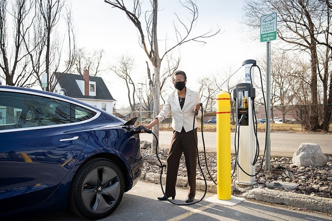 Person plugs in a blue car at an electric car charging station