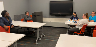 SUNY Chancellor Jim Malatras talks with students inside a conference room.
