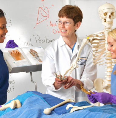 Two female students work with female teacher in a medical lab class looking at skeletons and bone structures.