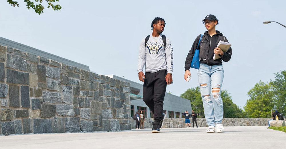 Male and female students walk outside along stone wall.