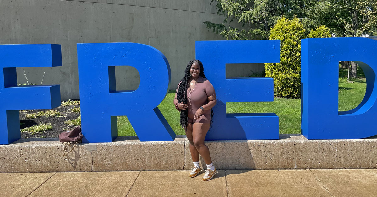 Tanique McLune in front of stonr FRED sign at SUNY Fredonia.
