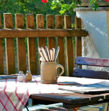 Backyard wooden dining table in front of fence and near a tree.